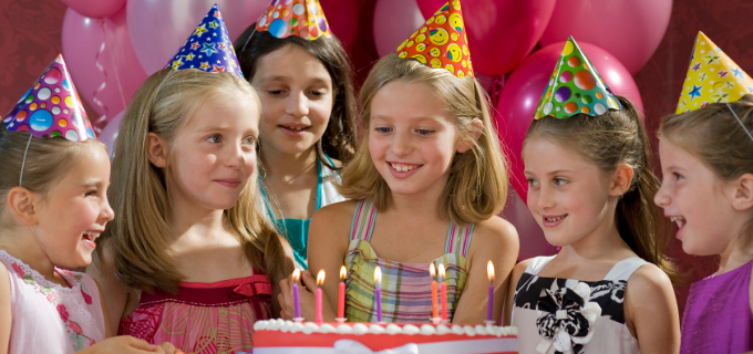 Young girls at a birthday party with cake